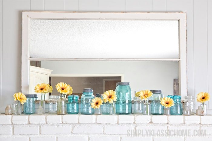 Several glass vases of flowers on a kitchen counter