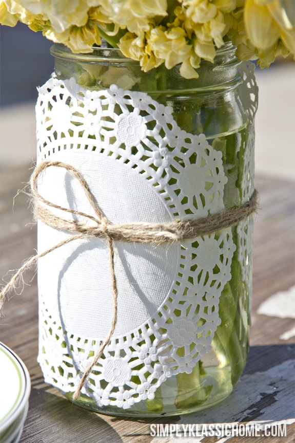 A doily covered mason jar vase filled with flowers sitting on a table