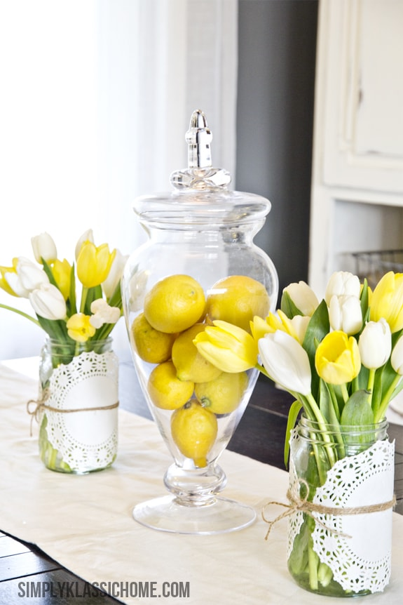 A vase of lemons with flowers
