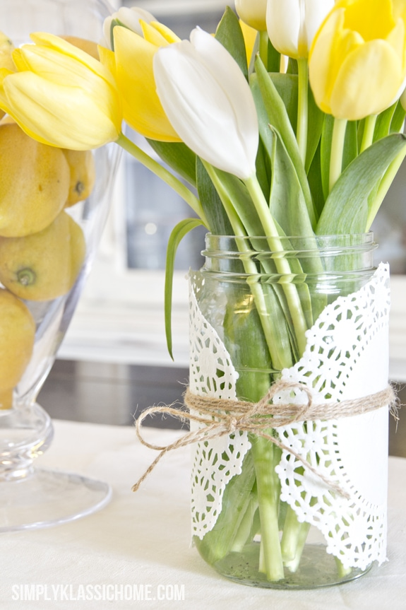A doily covered vase filled with flowers