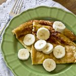 A green plate with pancakes and bananas