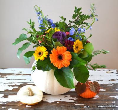 A bouquet of flowers in a pumpkin on a table