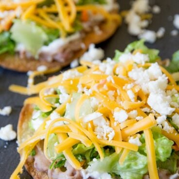 Baked tostadas with beans, lettuce and cheese social media image.
