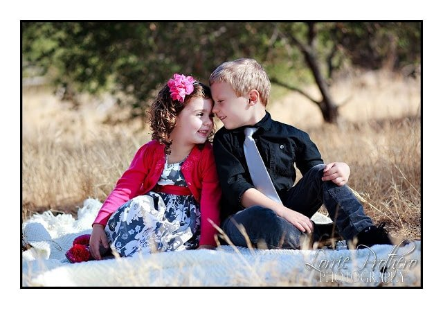 A little girl and boy sitting in the grass