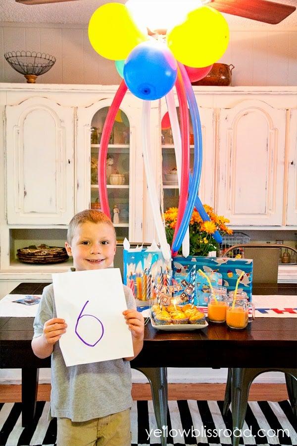 Boy smiling next to birthday decorations