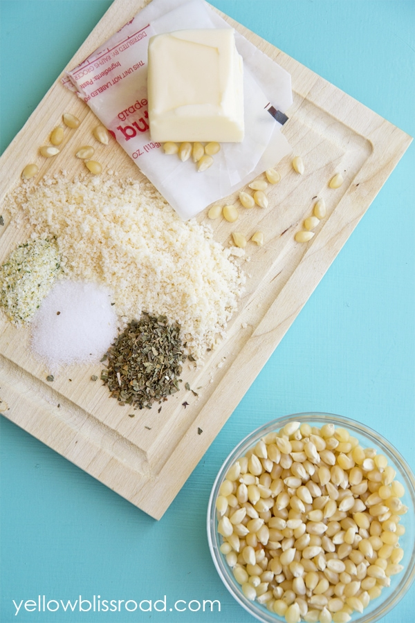 A cutting board with popcorn kernels, cheese, butter, and seasonings