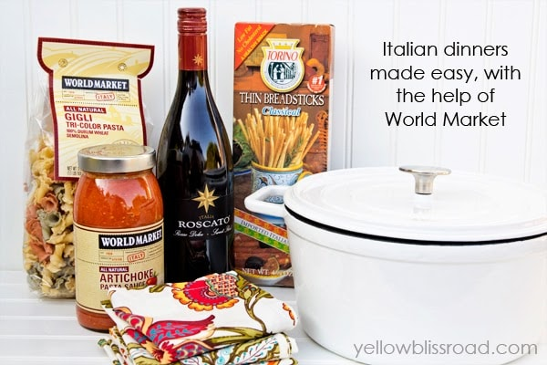 Wine, pasta sauce, pasta, and pot sitting on a table