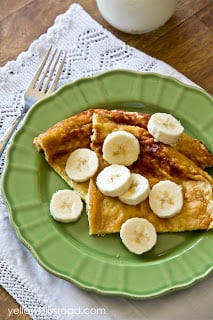 Pancake and bananas on a green plate on a table