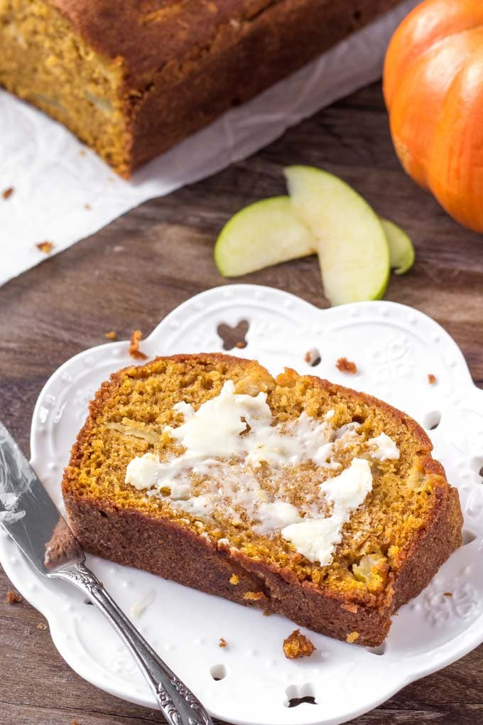 A slice of Pumpkin Bread with Apples spread with butter.