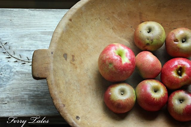 Apples sitting in a wooden bowl