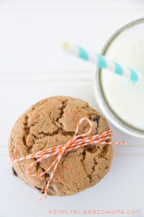 Stack of cookies on a table with a cup of milk