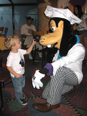 A young boy meeting Goofy