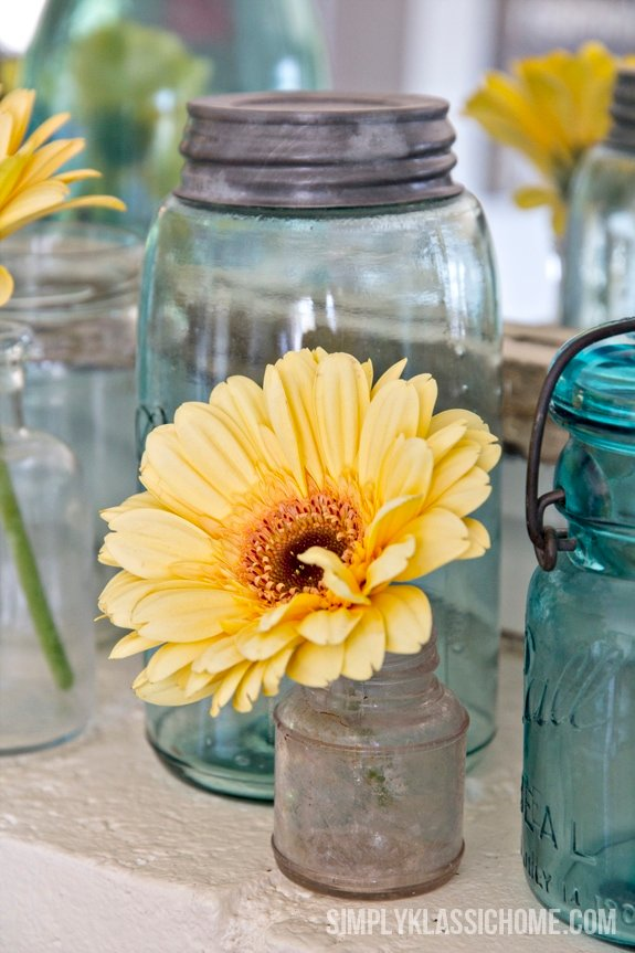 A glass vase with a yellow flowers sitting on a table