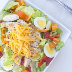 A plate of salad with chicken, cheese, and veggies