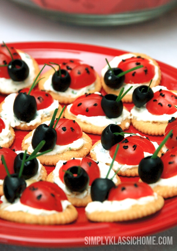 Crackers, tomatoes, and olives that look like ladybugs