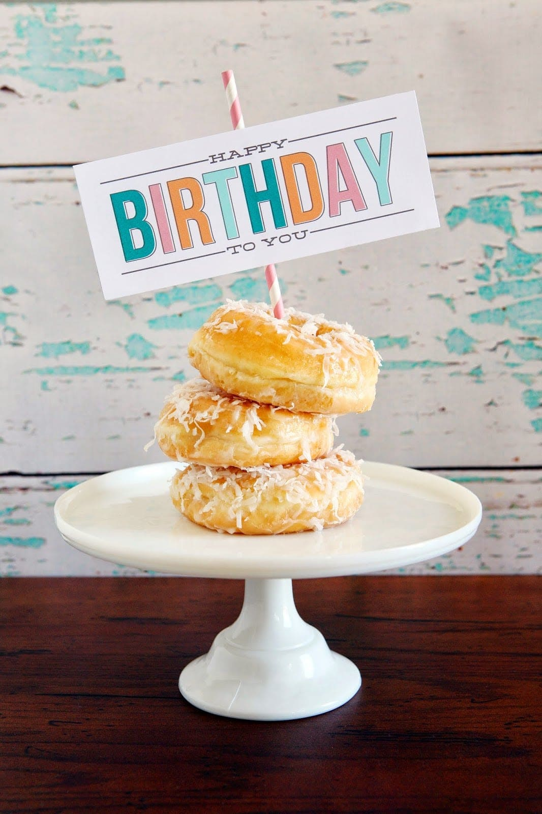 Donuts on a cake stand with a happy birthday sign