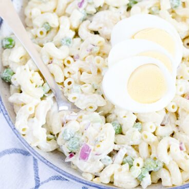 Bowl of macaroni salad, with sliced eggs and a metal spoon