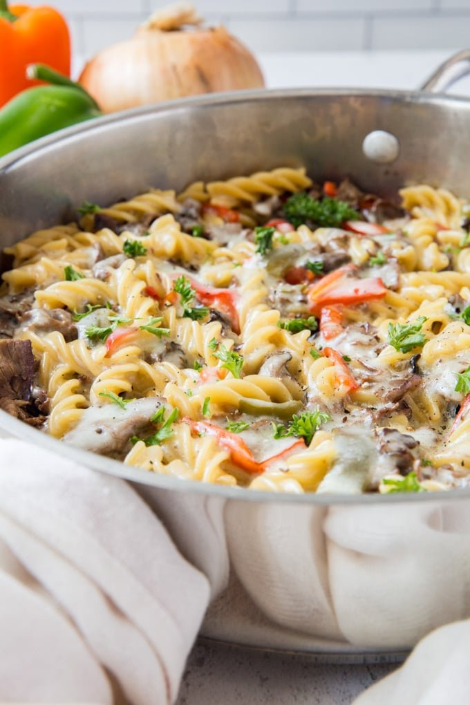 A stainless steel skillet with philly cheesesteak pasta