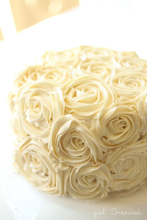 A white cake with frosting roses