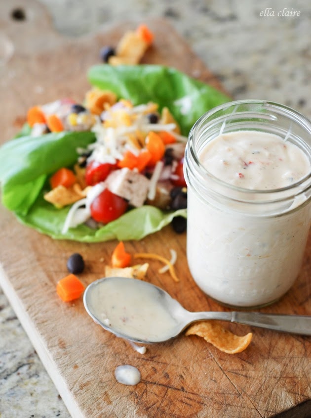 A jar of dressing next to a lettuce wrap on a wooden cutting board