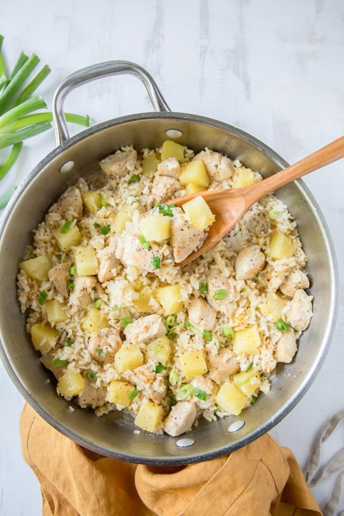 silver pan with rice, chicken and pineapple, with a wooden spoon.