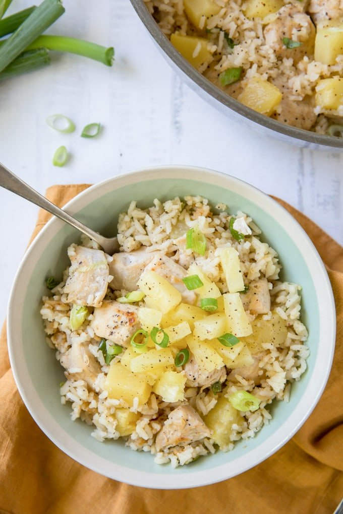 A blue bowl with chicken, pineapple and rice topped with sliced green onions. A fork sticks out of the bowl.