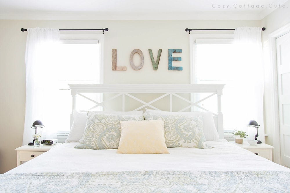 """A bed with a sign \""""LOVE\"""" above"""