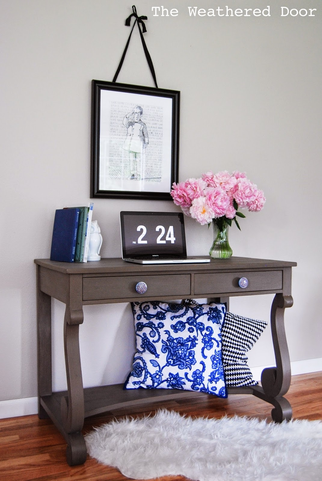 Wooden desk with laptop and flowers on top