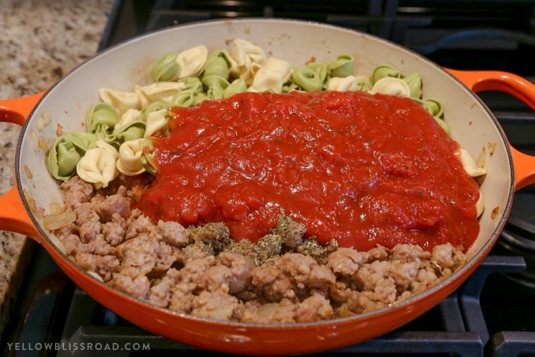 Ingredients for Italian Sausage and Tortellini in a large skillet.