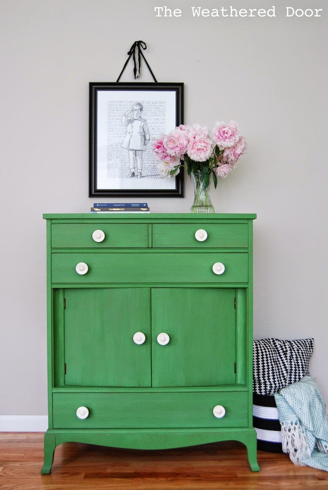 A green dresser with flowers and art on the wall on top