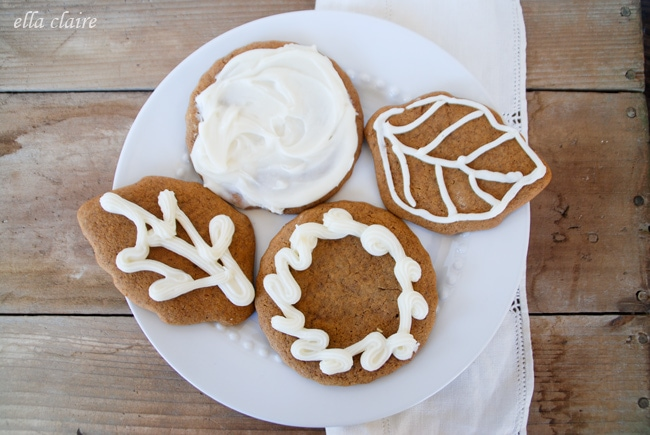 A plate of cookies with frosting sitting on top of a wooden table