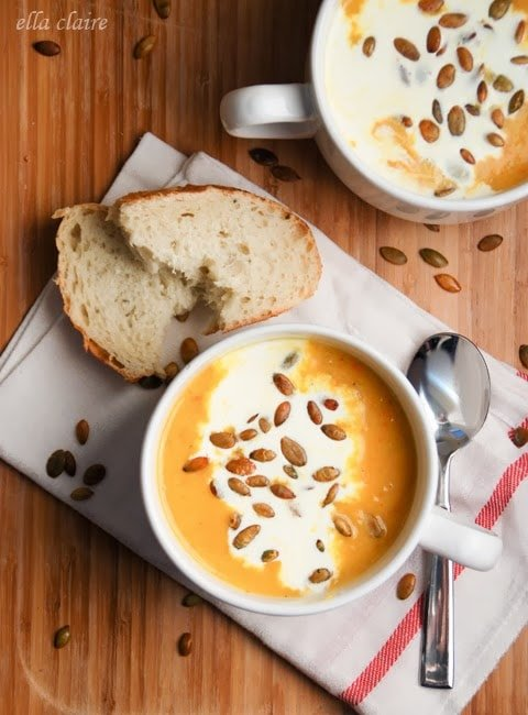 A bowl of pumpkin bisque on a wooden table, with bread