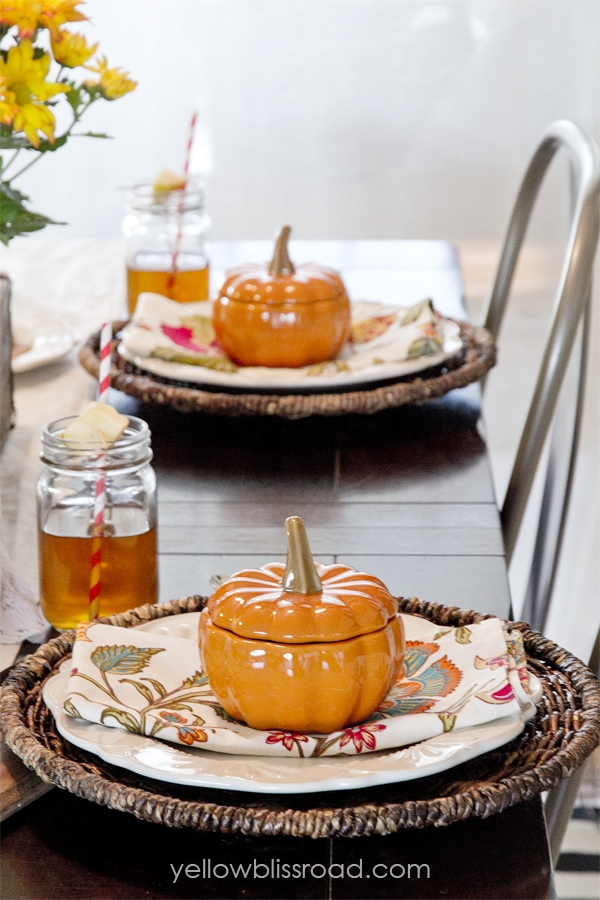 A table with pumpkin autumn decor and glasses of tea