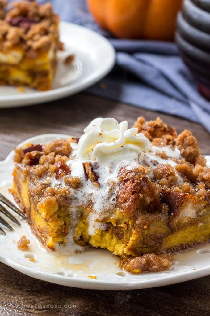 A delicious slice of Pumpkin Pie French Toast Bake recipe with whipped cream and maple syrup.