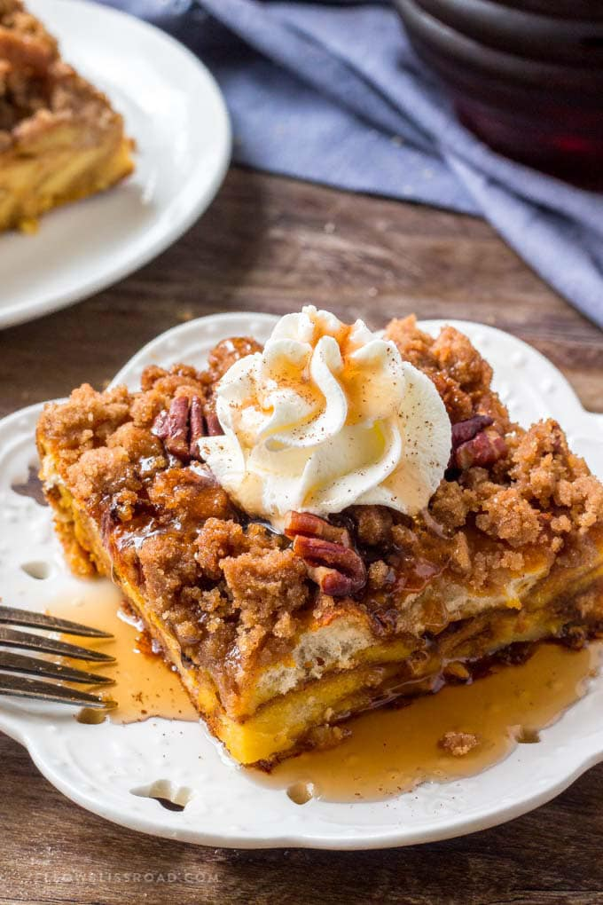 A slice of Pumpkin Pie Baked French Toast with whipped cream and maple syrup.