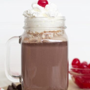 Hot chocolate in a glass mug with whipped cream on top