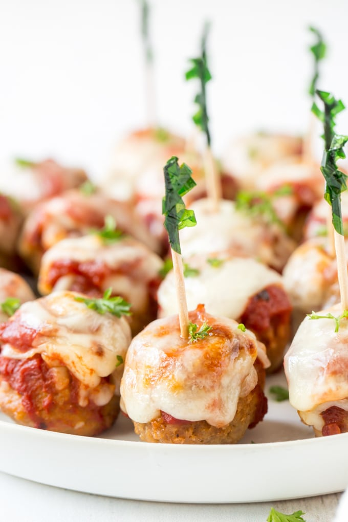 A close up image of meatballs with marinara and cheese and toothpicks stuck in them.