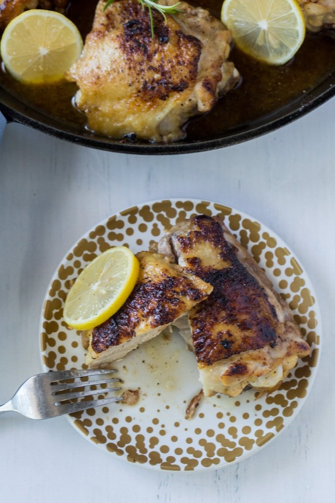 An overhead image of a chicken thigh cut in half with a slide of lemon.