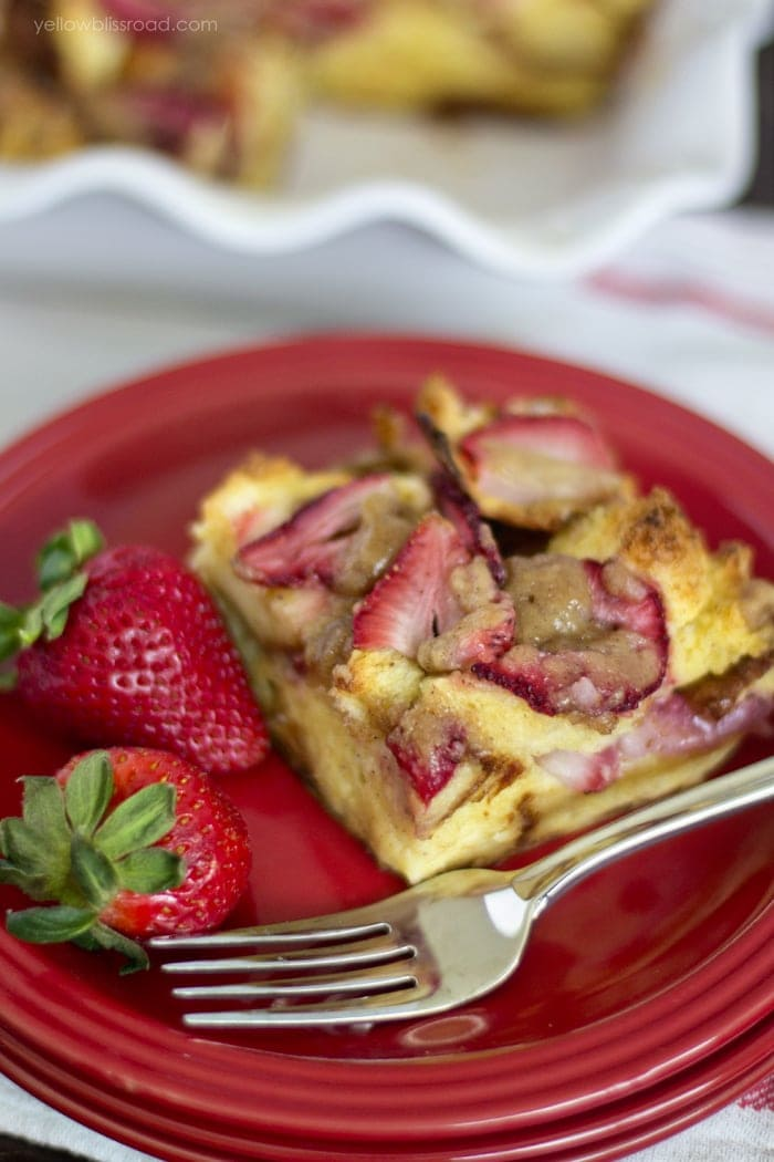 A slice of Strawberry Baked French Toast on a red plate with a fork.