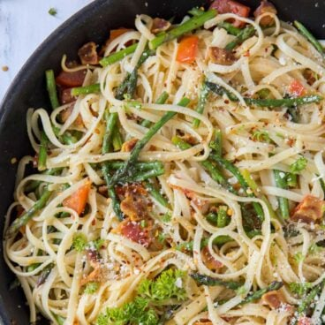 A bowl of asparagus and pasta, with Bacon