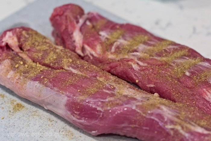 Raw pork tenderloin coated with poultry seasoning