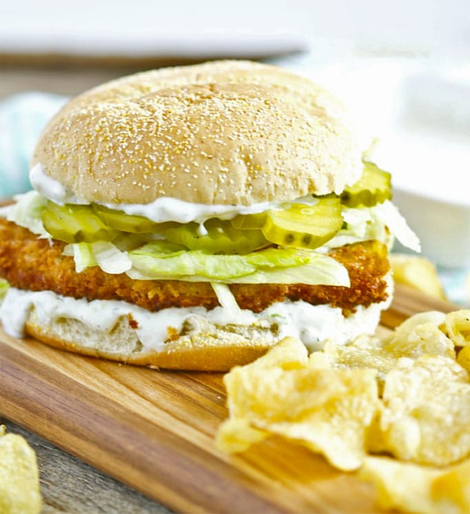 A sandwich with crispy chicken, dill pickles and lettuce on a wooden cutting board next to a pile of potato chips