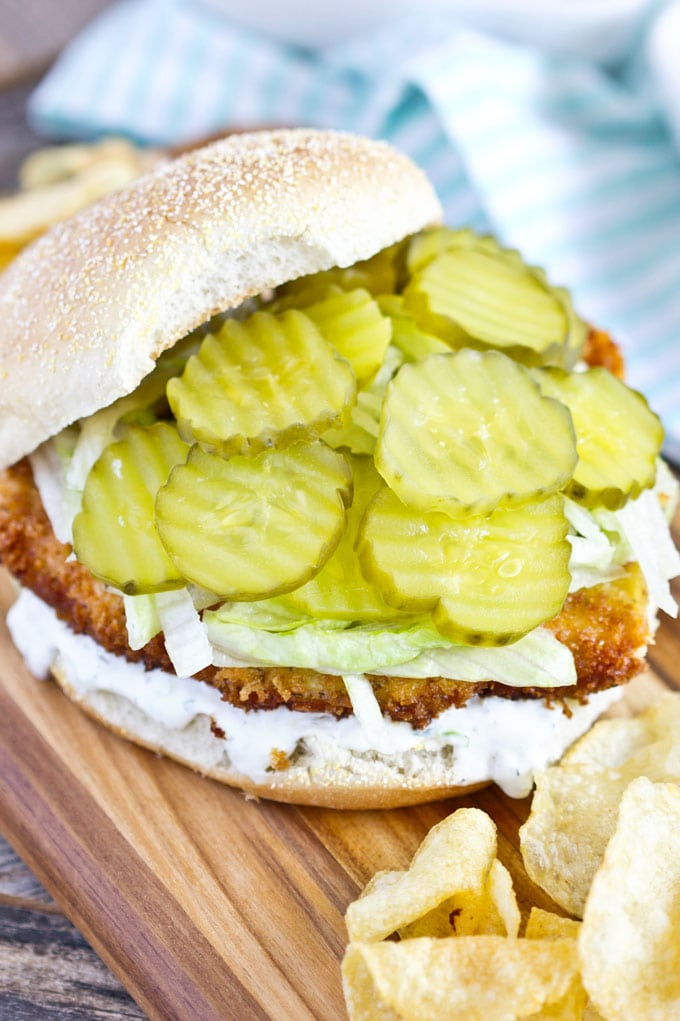 open faced chicken sandwich piled with dill pickles on a bun