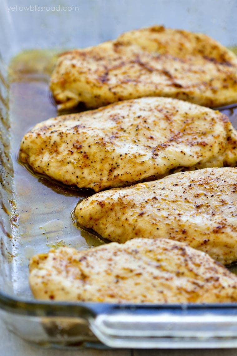 4 cooked chicken breasts with seasoning in a clear glass baking dish