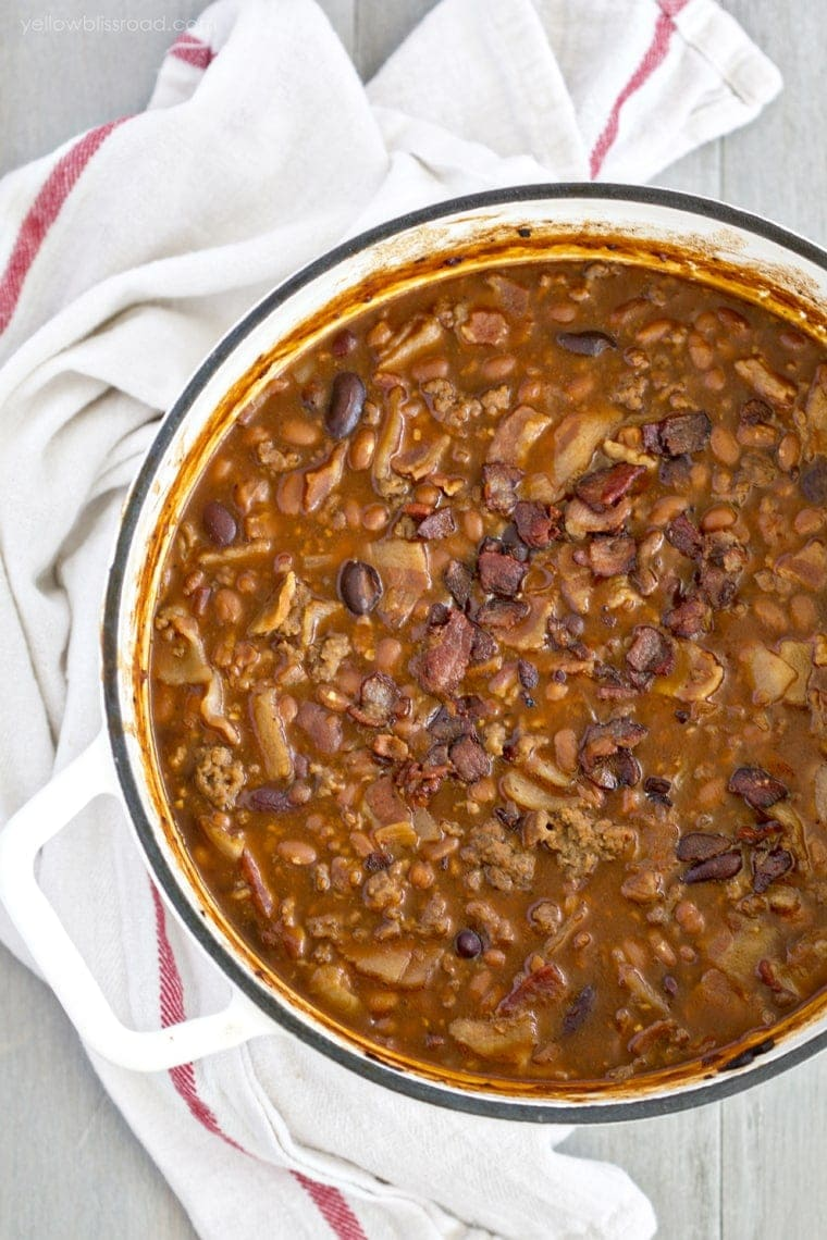 An overhead shot of a large white pot with baked beans, beef and bacon