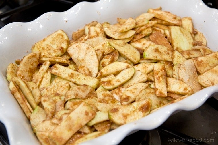 Sliced apples with brown sugar and cinnamon in a large baking dish.