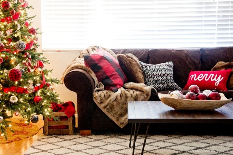 Chrismtas tree with buffalo check pillows on Brown sofa