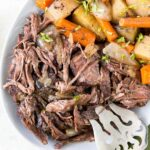 pot roast with carrots, potatoes, onions on a white plate, silver fork