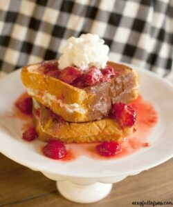 Cream Cheese Stuffed French Toast on a raised platter, topped with whipped cream