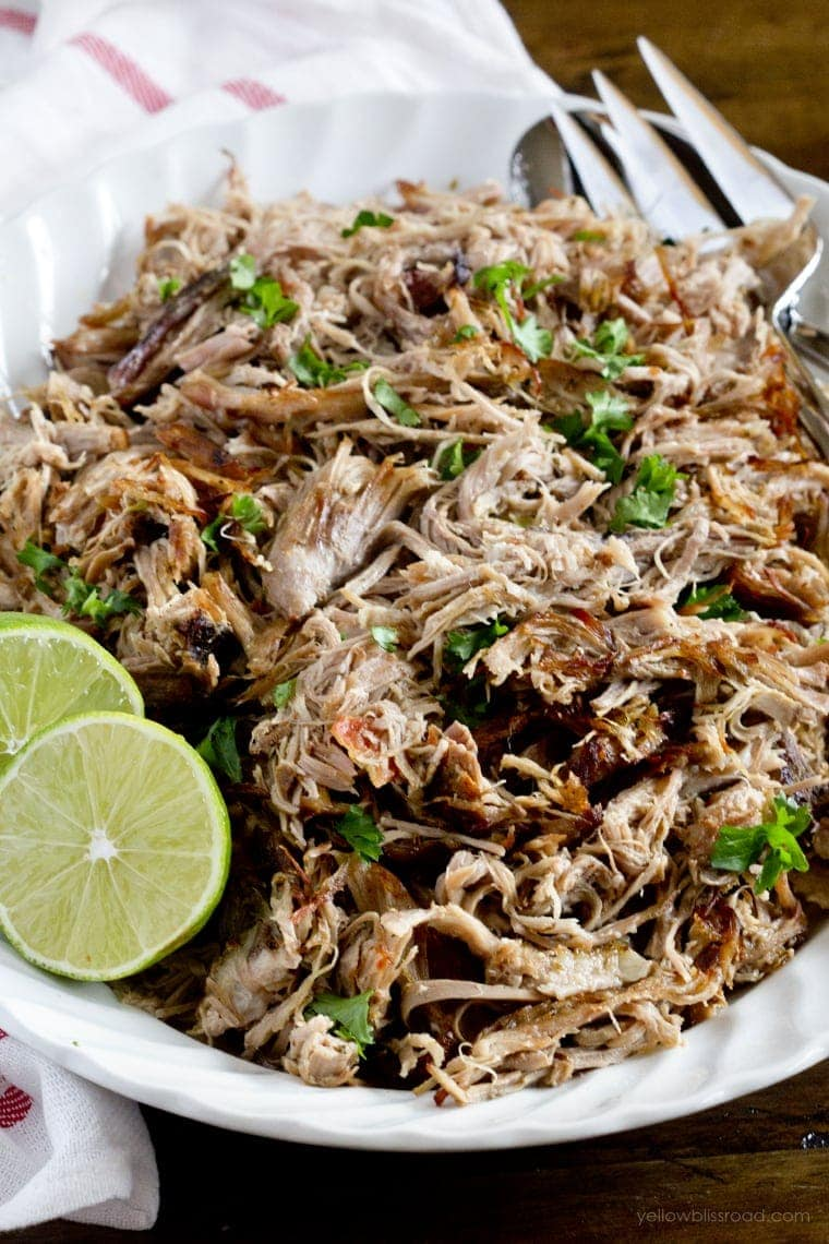 Easy Slow Cooker Carnitas shredded on a plate with limes and parsley garnish